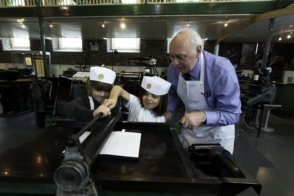 Eric Davis (9) and Branon Noble (8) learn about printing from retired engineer Eddie Gahan. Pic: John T Ohle Photography, courtesy of National Heritage Week.