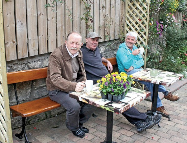 Pictured from left to right: Shay Connolly, Eamonn Dolphin and Joe Donnelly enjoy a cup of tea on the new bench dedicated to Maureen.