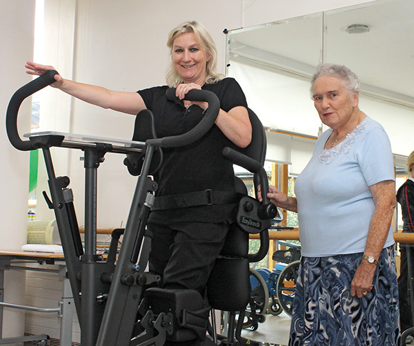 Barbara Sheerin and Gladys Kingston demonstrate the EasyStand Glider, a machine that is used to help patients learn how to walk again in the Royal Hospital, Donnybrook.