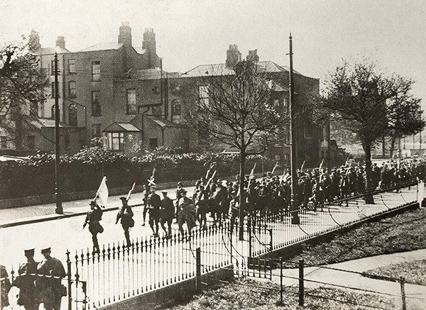 Pictured Above: After the surrender – Rebels under the command of De Valera (marked with white x) marching on Grand Canal Street. Picture courtesy of the National Library.